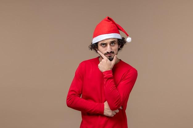Vorderansicht junger mann mit denkendem ausdruck auf weihnachtsemotionsfeiertag des braunen hintergrunds
