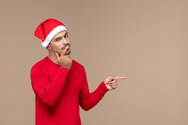 Vorderansicht junger mann mit denkendem gesicht auf braunem hintergrundemotionsweihnachtsfeiertag