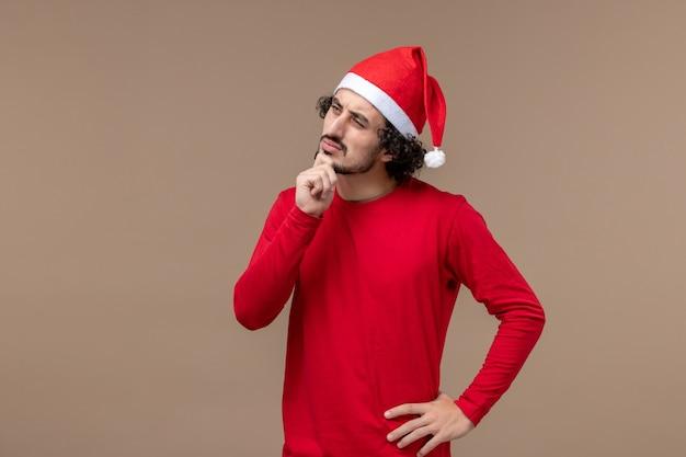 Vorderansicht junger mann mit denkendem gesicht auf braunem hintergrundweihnachtsemotionsfeiertag