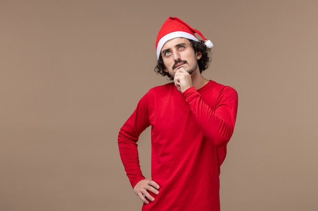 Vorderansicht junger mann mit denkendem gesicht auf der weihnachtsemotion des braunen hintergrundfeiertags