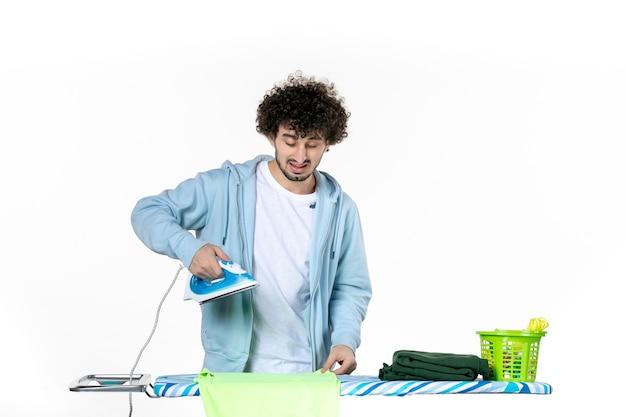 Vorderansicht junger mann mit eisen auf weißem hintergrund eisenfarbe mann wäsche kleidung hausarbeit emotion