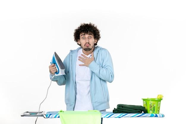 Vorderansicht junger mann mit eisen auf weißem hintergrund eisenfarbe mann wäsche kleidung hausarbeit reinigung emotion