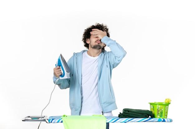 Vorderansicht junger mann mit eisen auf weißem hintergrund eisenfarbe mann wäsche kleidung hausarbeit reinigung emotionen