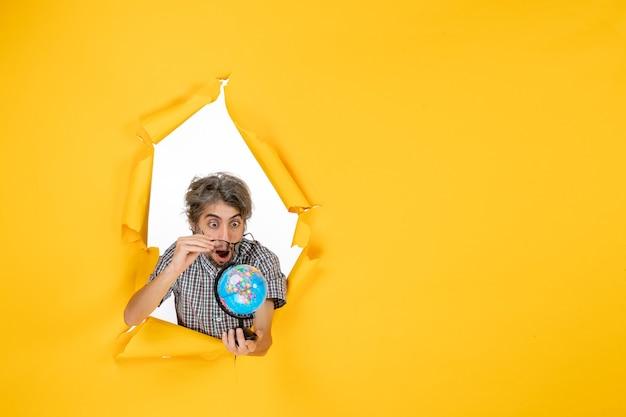 Vorderansicht junger mann mit erdkugel auf gelbem hintergrund farbe weihnachtsplaneten urlaub welt land emotionen
