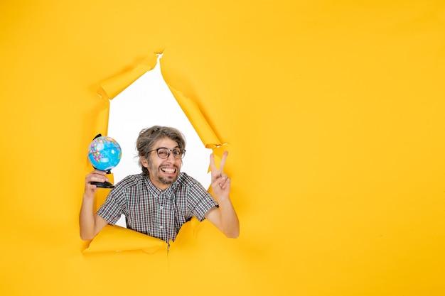 Vorderansicht junger mann mit erdkugel auf gelbem hintergrund farbe weihnachtsplaneten urlaub weltland