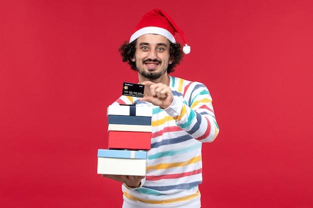 Vorderansicht junger mann mit feiertagsgeschenken und bankkarte auf roter wand neujahrsgeldrot