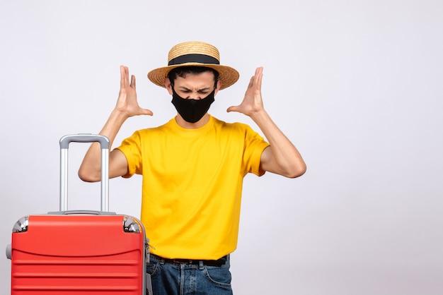 Vorderansicht junger mann mit gelbem t-shirt und rotem koffer verwirrend