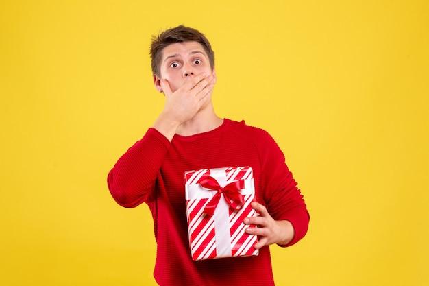 Vorderansicht junger mann mit geschenk überrascht auf gelbem hintergrund
