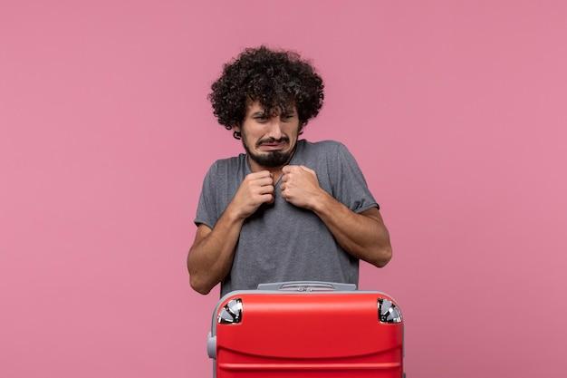 Vorderansicht junger mann mit großer roter tasche, der sich auf die reise vorbereitet und auf dem rosa raum posiert