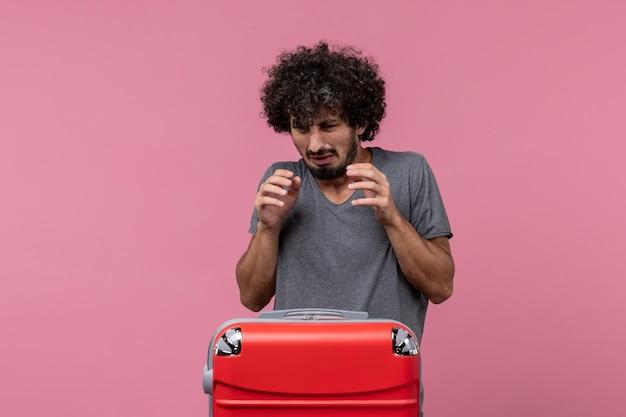 Vorderansicht junger mann mit großer roter tasche, die sich auf die reise vorbereitet und auf rosa schreibtisch posiert