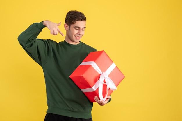 Vorderansicht junger mann mit grünem pullover, der auf geschenk auf gelb zeigt
