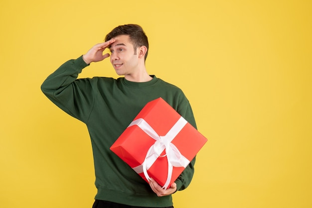 Vorderansicht junger mann mit grünem pullover, der etwas auf gelb betrachtet