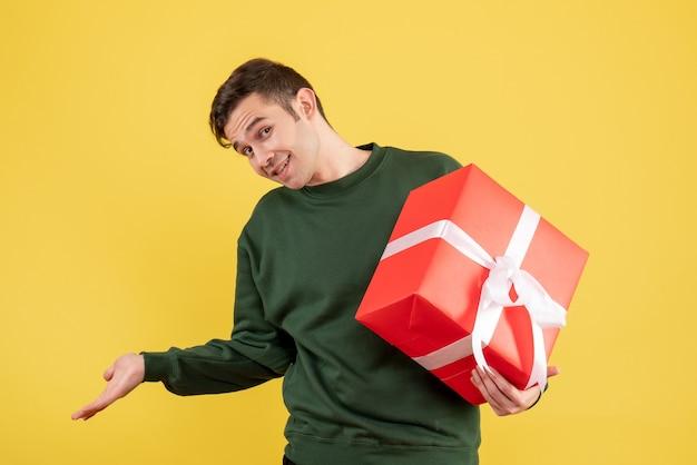 Vorderansicht junger mann mit grünem pullover, der geschenk auf gelb hält