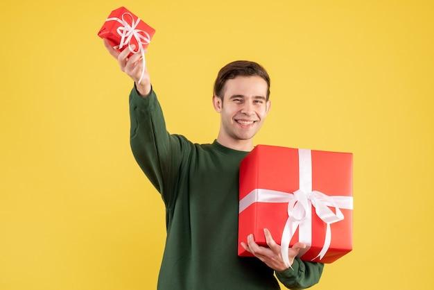 Vorderansicht junger mann mit grünem pullover, der große und kleine geschenke hält, die auf gelb stehen