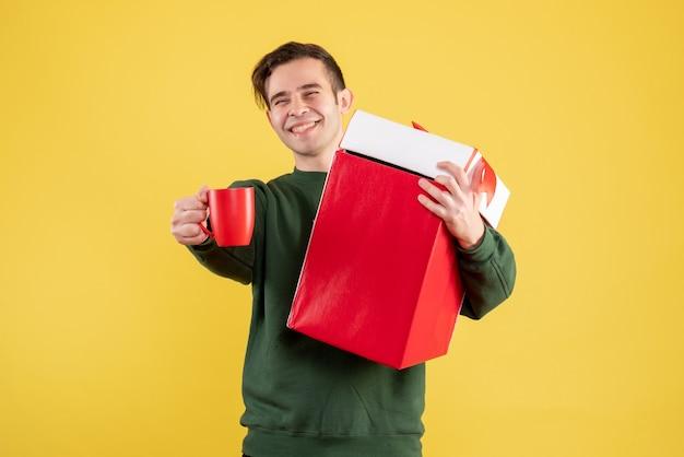 Vorderansicht junger mann mit grünem pullover, der großes geschenk und rote tasse steht auf gelb hält