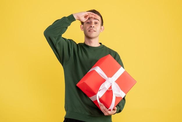 Vorderansicht junger mann mit grünem pullover, der hand auf seine stirn auf gelb legt