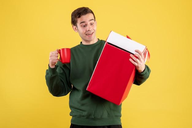 Vorderansicht junger mann mit grünem pullover, der rote tasse betrachtet, die auf gelb steht