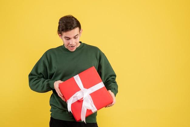 Vorderansicht junger mann mit grünem pullover, der sein geschenk auf gelb betrachtet