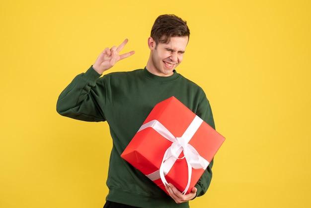 Vorderansicht junger mann mit grünem pullover, der siegeszeichen auf gelb macht