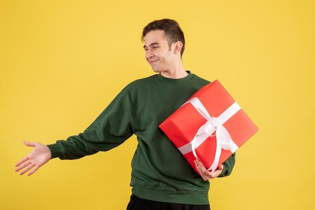 Vorderansicht junger mann mit grünem pullover geben hand, die auf gelb steht