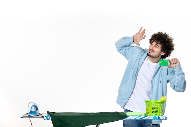Vorderansicht junger mann mit grüner bankkarte auf weißem hintergrund geldwäsche hausarbeit menschliche reinigung farbe bügeln emotionen