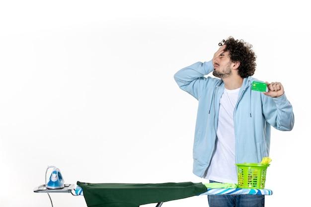 Vorderansicht junger mann mit grüner bankkarte auf weißem hintergrund wäsche hausarbeit menschliches geld emotion farbe bügeln