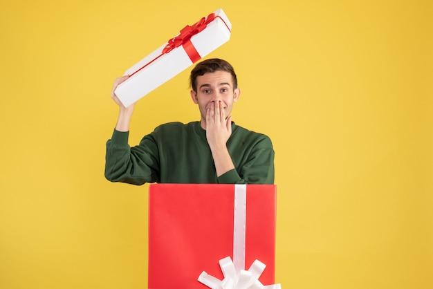Vorderansicht junger mann mit kastenabdeckung, die hand an seinen mund setzt, der hinter großer geschenkbox auf gelb steht