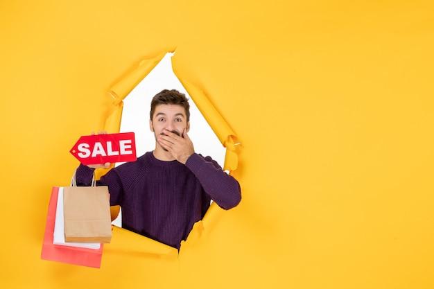 Vorderansicht junger mann mit kleinen paketen und verkaufsschreiben auf gelbem hintergrund neujahr geschenk farbe weihnachtsgeschenk weihnachten