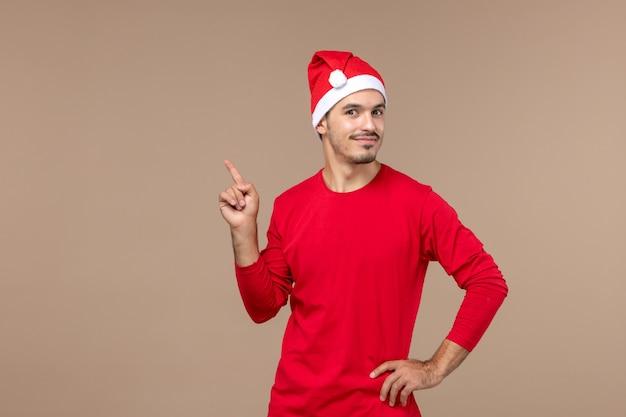 Vorderansicht junger mann mit lächelndem ausdruck auf männlicher emotionsfeiertagsfarbe des braunen hintergrunds