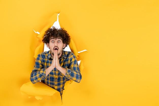 Vorderansicht junger mann mit lockigem haar auf gelbem, zerrissenem hintergrund
