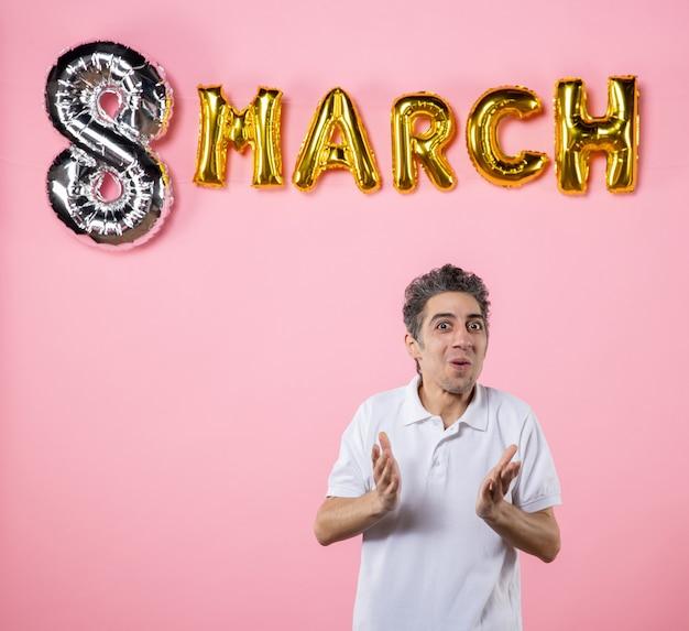 Vorderansicht junger mann mit marschdekoration auf rosa hintergrund modell gleichheit emotion frauentag party urlaub sinnliche farben