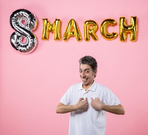 Vorderansicht junger mann mit marschdekoration auf rosa hintergrund modell gleichheit emotionen frauentag party urlaub sinnliche farbe