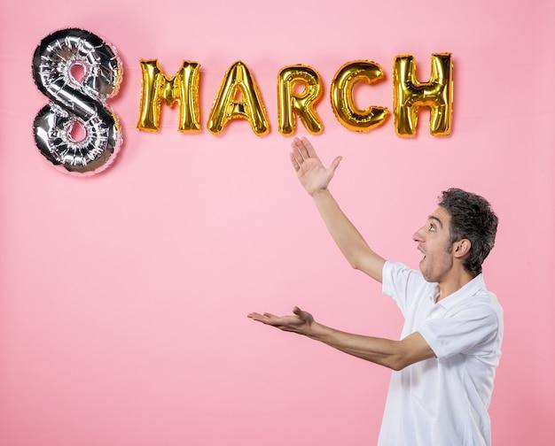 Vorderansicht junger mann mit marschdekoration auf rosa hintergrund urlaub glamour farbe womens day party feminines modell sinnliche emotion