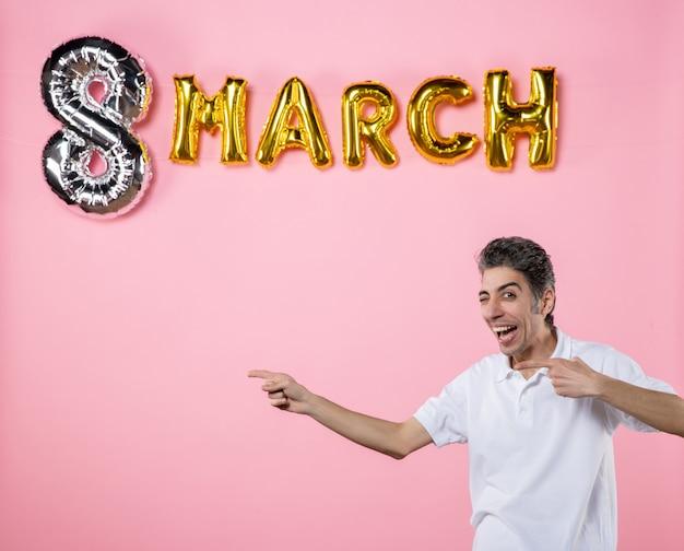 Vorderansicht junger mann mit marschdekoration auf rosa hintergrund urlaub glamour farbgleichheit frauentag party modell sinnliche emotion