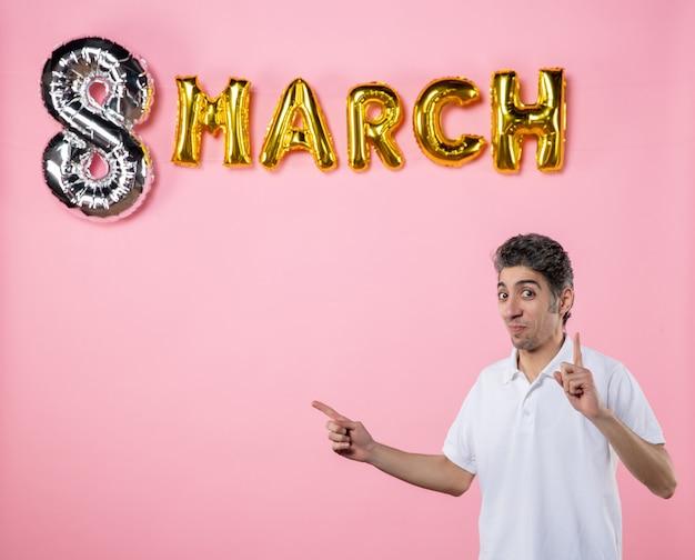 Vorderansicht junger mann mit marschdekoration auf rosa hintergrund urlaub glamour gleichheit emotion frauentag sinnliche farbe party feminines modell