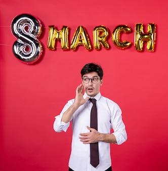 Vorderansicht junger mann mit marschdekoration auf rotem hintergrund farbe präsentieren womans day urlaub sinnliche mode leidenschaft geschenk