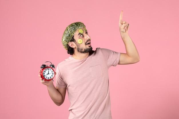 Vorderansicht junger mann mit maske auf seinem gesicht, das uhr auf rosa hintergrund hält