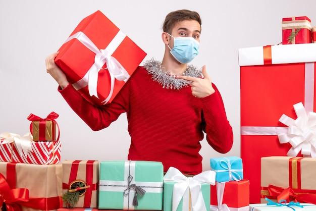 Vorderansicht junger mann mit maske, die auf geschenk zeigt, das um weihnachtsgeschenke sitzt