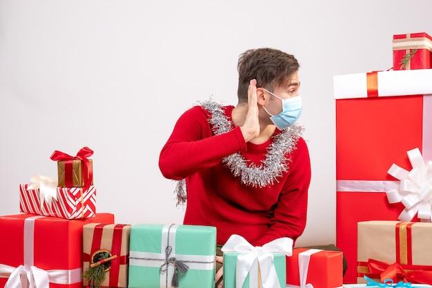 Vorderansicht junger mann mit maske, die etwas hört, das um weihnachtsgeschenke sitzt