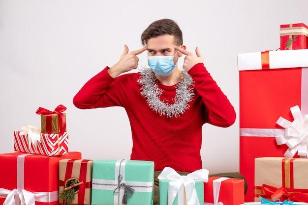 Vorderansicht junger mann mit maske, die finger zu seiner schläfe setzt, die um weihnachtsgeschenke sitzt