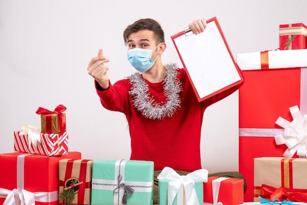 Vorderansicht junger mann mit maske, die fingerherzgeste macht, die auf bodenweihnachtsgeschenken sitzt