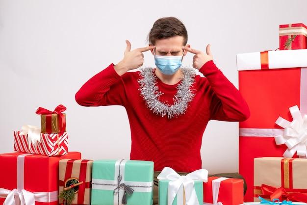 Vorderansicht junger mann mit maske, die fingerpistolen zu seinem tempel setzt, der um weihnachtsgeschenke sitzt