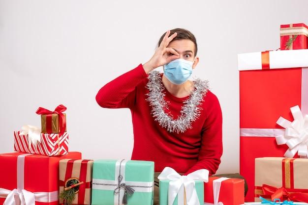 Vorderansicht junger mann mit maske, die okey zeichen vor seinem auge setzt, das um weihnachtsgeschenke sitzt