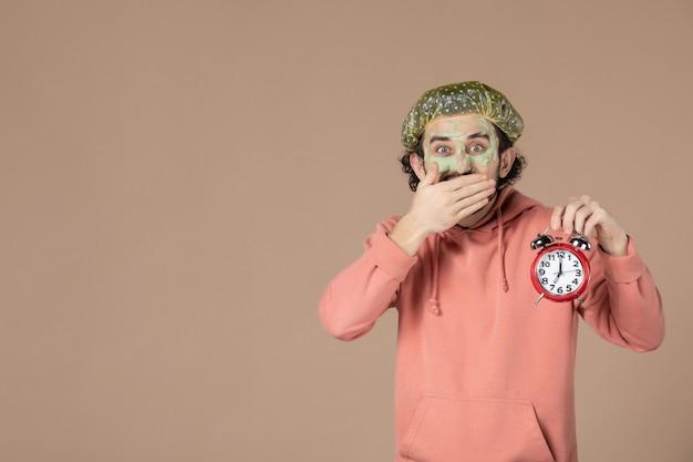 Vorderansicht junger mann mit maske, die uhren auf braunem hintergrund hält spa-therapie-salon-haut-körperpflege-gesichtsbehandlung