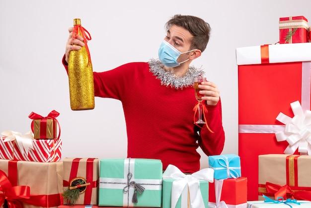 Vorderansicht junger mann mit maske, die um weihnachtsgeschenke röstend sitzt