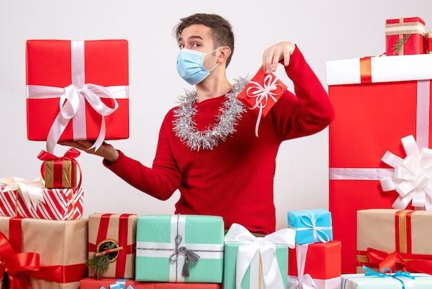 Vorderansicht junger mann mit maske, die weihnachtsgeschenke hält, die um weihnachtsgeschenke sitzen