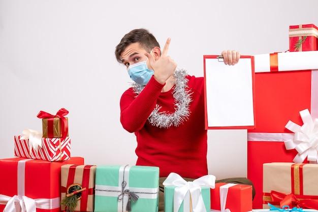 Vorderansicht junger mann mit maske, die zwischenablage hält, die auf bodenweihnachtsgeschenken sitzt