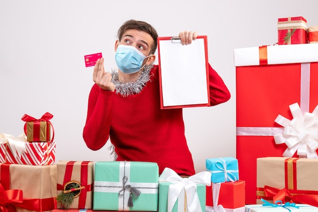 Vorderansicht junger mann mit maske, die zwischenablage und karte hält, die um weihnachtsgeschenke sitzen