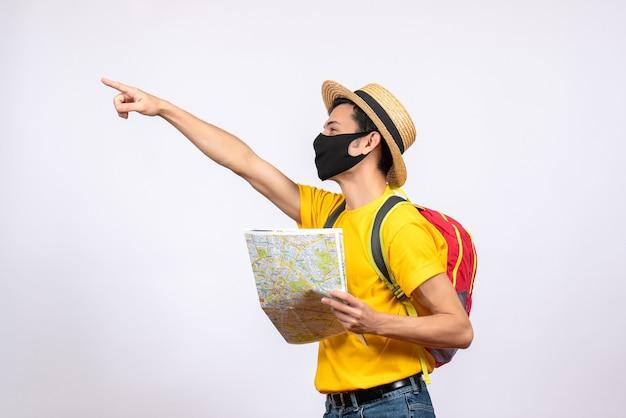 Vorderansicht junger mann mit maske und rotem rucksack, der etwas zeigt