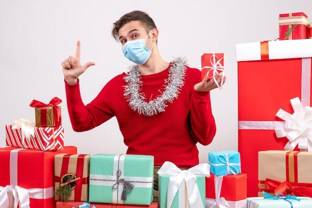 Vorderansicht junger mann mit medizinischer maske, die um weihnachtsgeschenke sitzt